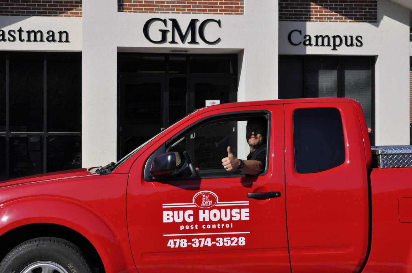 Bug House Eastman pest control employee driving company truck