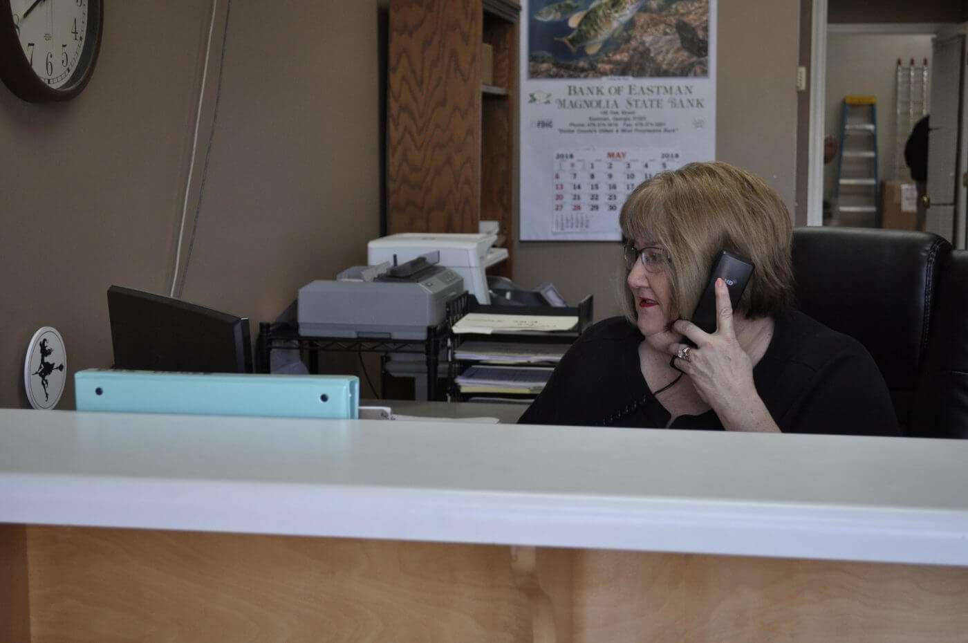 Bug House Eastman pest control employee on the phone with a client
