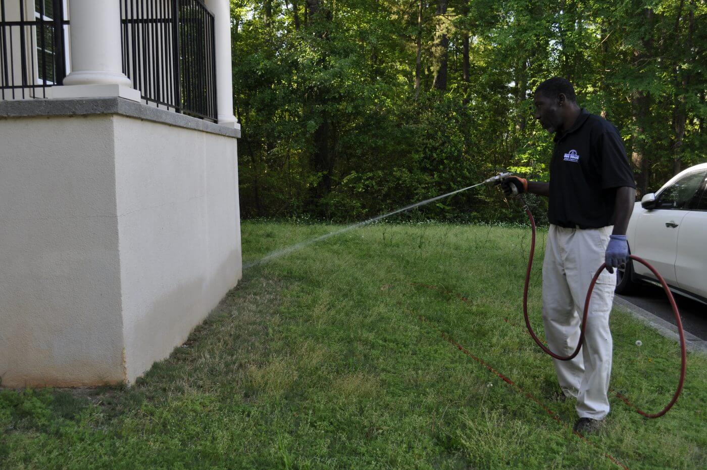 Bug House Milledgeville employee working on pest control outside